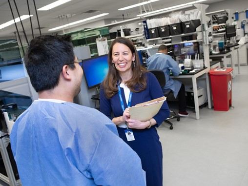 Genetic counselor Bethany Tucker holds a file folder while discussing the gene-editing tool CRISPR with a colleague in a genetics lab. Another colleague sits at a lab bench, facing away from the camera.