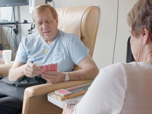 David Huiskes plays cards in an infusion room while he undergoes cancer treatment. He is looking down while his opponent has her back to the camera.